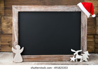 Christmas chalkboard with decoration. Santa hat, stars,  Wooden Background. Vintage Rustic Style.