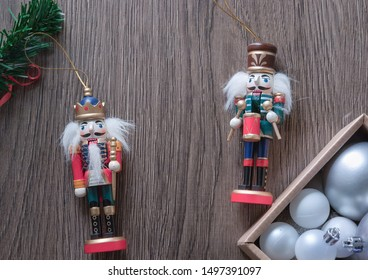Christmas characters, nutcrackers on a wooden table with a box of balls