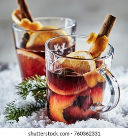 Christmas Cheer with hot spicy mulled red wine or Gluhwein with oranges, star anise, sugar, and stick cinnamon on a bed of winter snow