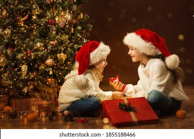 Christmas Child Girl opening Box and giving Gift Toy to Sister. Happy Children in Santa Hat next to Xmas Tree. Fairy Magic Interior, Indoor Lights