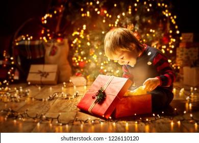 Weihnachtskinderoffenes Geschenk, Happy Baby Boy mit Blick auf Magic Light in Box, Kind sitzend vor Weihnachtsbaum