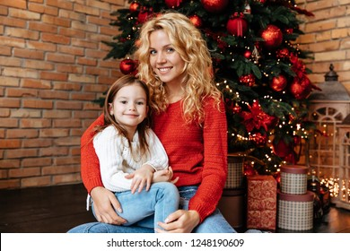 Christmas. Childhood. Home. Little girl and her mom are looking at camera and smiling while sitting near the Xmas tree