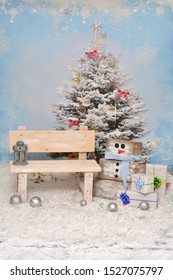 Christmas children blue snowy background for mini saisson, set up, with little homemade banch and wooden snowman