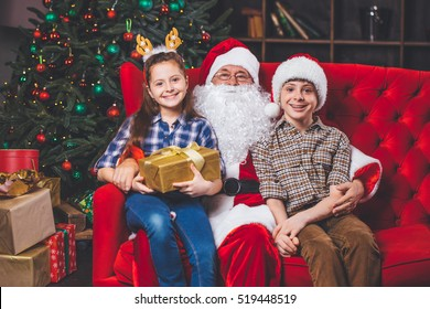 Christmas, children and gifts. Santa Claus brought gifts to children. Joyful kids with gifts hugging Santa Claus