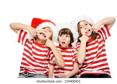 Christmas children having fun with xmas hats, gift box and matching t-shirts isolated on white background
