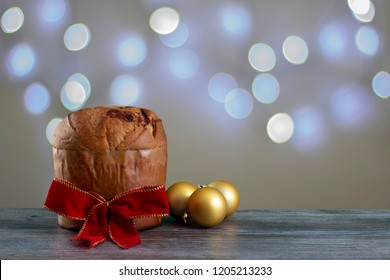 Christmas chocolate cake panettone with a red ribbon in a christmas light background with ornament or panetone chocotone