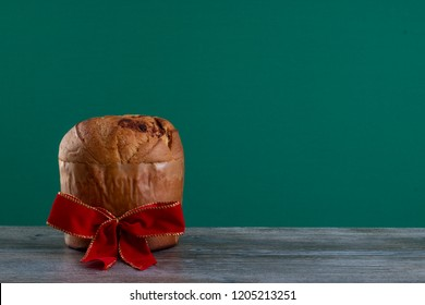 Christmas chocolate cake panettone with a red ribbon in a chroma background or panetone chocotone