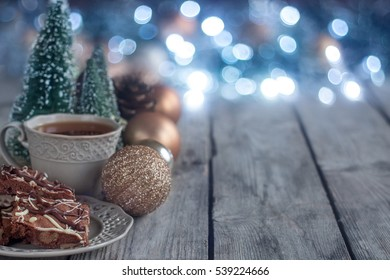 Christmas chocolate cookies on wooden table with tea, balls and defocused lights. Copyspace background.