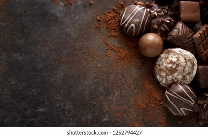 christmas chocolate cookies and pralines on a dark stone slab with large copy space, high angle view from above