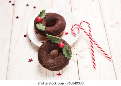 Christmas Chocolate donuts with candes on white wooden background