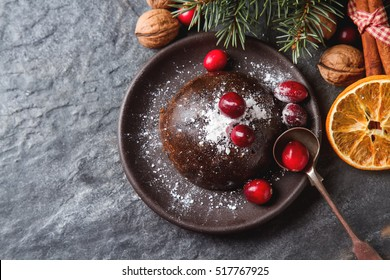 Christmas chocolate pudding with cranberries, walnuts, cinnamon, apples and oranges. Dark background