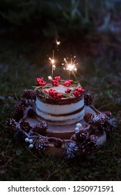 Christmas chocolate vanilla cake. Rustic homemade cake. Piece of cake. Vegan raw cake. Decorated rosemary and Christmas tree. Lights and sparkler. Candle and garland on the background.
