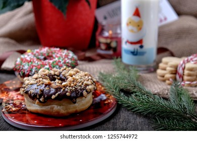 Christmas chokolate donuts with  glass of milk and candle on the background