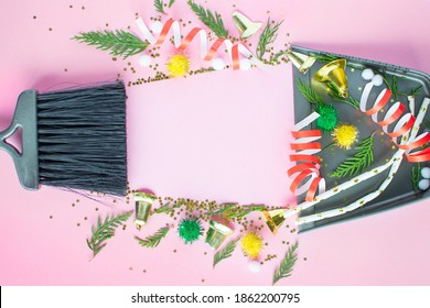 Christmas cleaning after. Cleaning tools broom and scoop and unused Christmas decorations after party top view flat lay on pink background. Concept of cleaning after holiday, clean up the mess.