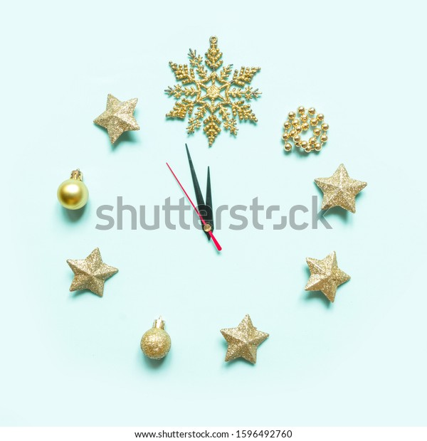 Christmas clock, dial, decorated with Christmas decorations, gold stars, bauble glitter, Christmas trees, creative flat composition with copy space, on neo mint background