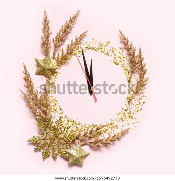 Christmas clock, dial, decorated with Christmas decorations, gold stars, bauble glitter, Christmas trees, creative flat composition with copy space, on pink  background