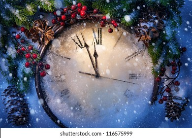 Christmas clock and fir branches covered with snow