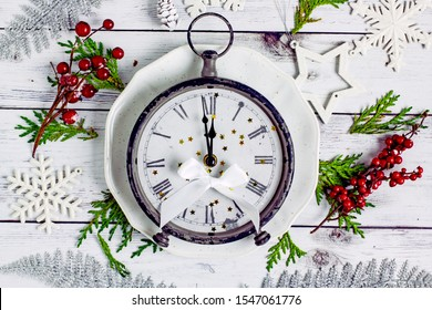 Christmas clock shows midnight. Antique clock with roman numerals on a white plate on a wooden light table near fir branches, cones, red berries, white snowflakes. Christmas and new year concept.