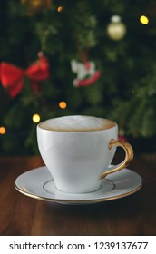 Christmas coffee on wooden table on christmas tree background