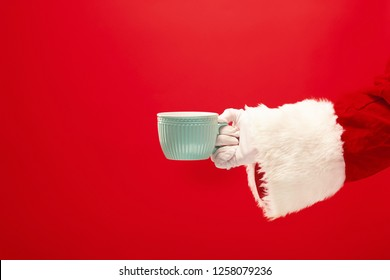 Christmas coffee. The Santa hand holding cup of cofee isolated on a red background with space for text. The season, winter, holiday, celebration, gift concept