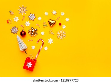 Christmas collection with gift box, snowflakes, candy cane on yellow background. Flat lay. Top view.