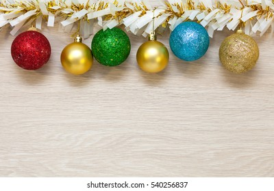 Christmas colored, multi-colored balls and garland, tinsel hanging on wooden background with space for text