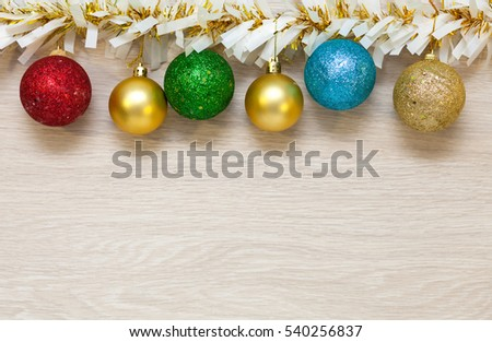 christmas colored multi colored balls and garland tinsel hanging on wooden background with