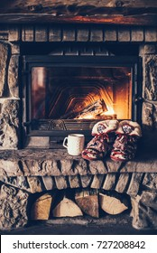 Christmas comfortable slippers by the warm cozy fireplace. Relaxing atmosphere in a chalet by authentic vintage fireside with a cup of hot drink. Winter and Christmas holidays concept.