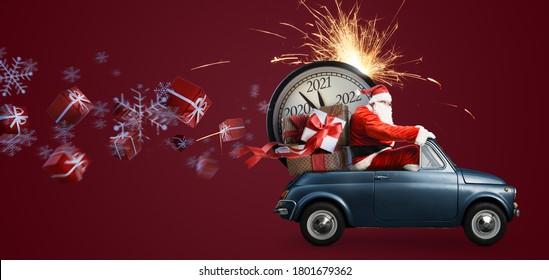Weihnachten kommt. Weihnachtsmann auf Spielzeugauto für Neujahr 2021 Geschenke und Countdown-Uhr auf rotem Hintergrund mit Feuerwerken
