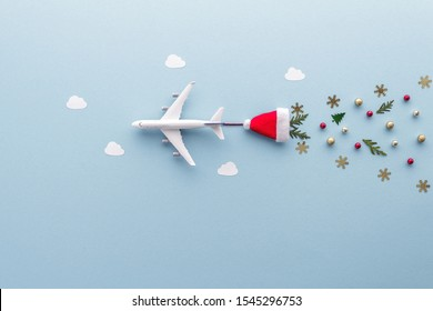 Christmas composition. Airplane flying in sky clouds fir star santa hat snowflake top view background with copy space for your text. Flat lay.