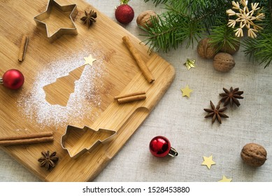Christmas composition around a shape of Christmas tree made of powdered sugar on wooden board, with traditional festive attributes, cookie cutters, cinnamon sticks, star anise, walnuts etc.