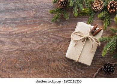 Christmas composition background on wood table with gift box and pine branches with cones. Top view with copy space, flat lay.