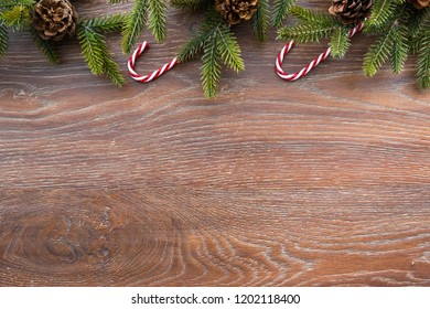 Christmas composition background on wood table with pine branches with cones and candy canes. Top view with copy space, flat lay.