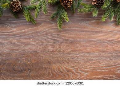 Christmas composition background on wood table with pine branches with cones. Top view with copy space, flat lay.
