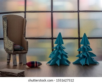 Christmas composition with blue paper trees, a recycled cardboard chair and small cushions. Stained glass window. Room for copy.