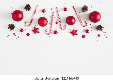 Christmas composition. Border made of red decorations on pastel gray background. Christmas, winter, new year concept. Flat lay, top view, copy space