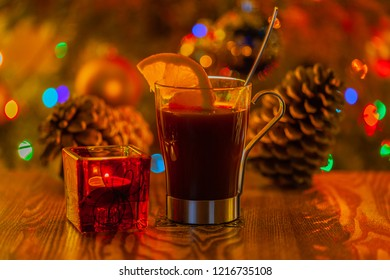 Christmas composition with the burning candle in candlestick and mulled wine against background of blurred pine cones, fir-tree and festive color bokeh