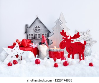Christmas composition with with a candle, elk and festive decorations оn the snow. Christmas or New Year greeting card.