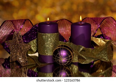 Christmas composition  with candles and decorations in purple and gold colors