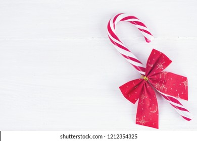 Christmas composition. Christmas candy cane on wooden white background. Flat lay, top view, copy space, background.