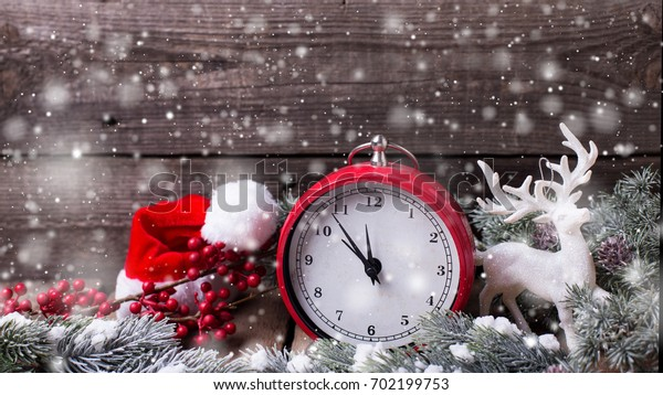 Christmas composition. Clock, deer, Santa hat, berries and branches fur tree on aged  wooden background. Selective focus. Place for text. Drawn snow effect.