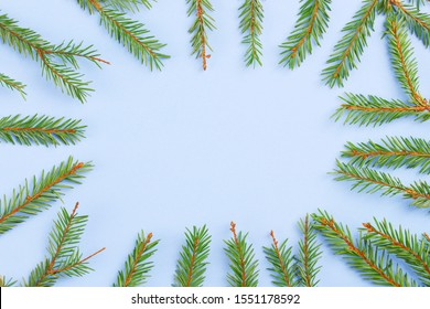 Christmas composition. Creative layout fir or spruce green branches on blue background. Square frame with christmas tree branch. Flat lay, top view, copy space. Pastel colors, trendy minimal concept.