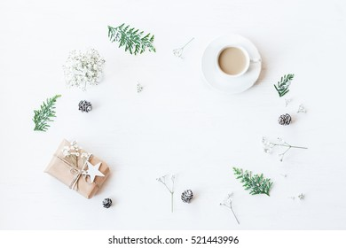 Christmas composition. Cup of coffee, christmas gift, pine cones, thuja branches and gypsophila flowers. Top view, flat lay