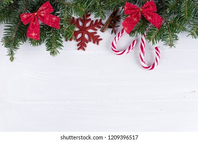 Christmas composition. Christmas decoration, ribbons, candy canes, fir branches on wooden white background. Flat lay, top view, copy space, background.