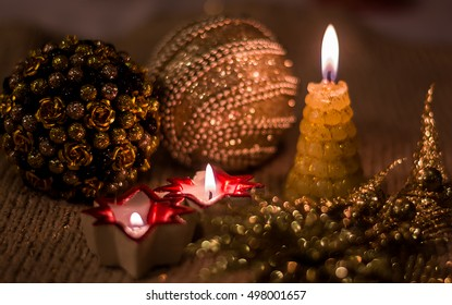 Christmas composition with Christmas decorations and candles, decorated in gold tones. Merry Christmas and Happy New Year