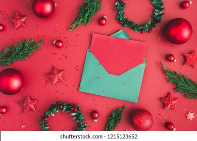 Christmas composition. Christmas decorations, fir tree branches, envelope on red background. Flat lay, top view, copy space