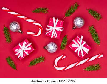 Christmas composition. Christmas decorations, fir tree branches, giftboxes and candycanes on red background. Flat lay.