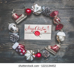 Christmas composition, Christmas decorations are lined up around the envelope on a wooden background, top view