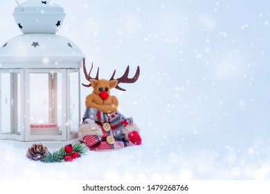 Christmas composition - deer, lantern with a burning candle and decorations under the Christmas tree