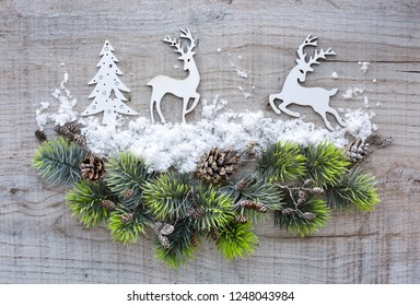Christmas composition with deers and spruce branches on a wooden table. Top view. Christmas or New Year greeting card.